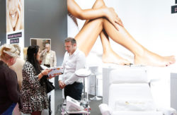 Photo: Sales talk in the background a poster with naked woman legs © Messe Düsseldorf